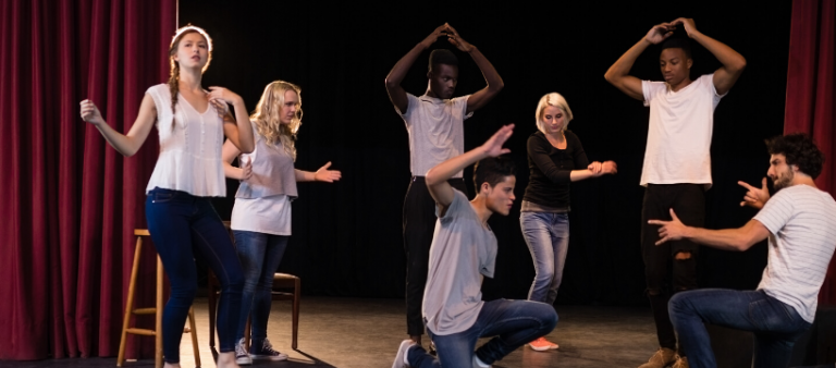 Group of female and male drama students performing
