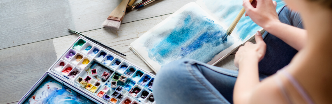 Female student using a watercolour brush to paint