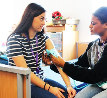 Female Health & Social Care student taking the blood pressure of another female student