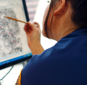 Criminologist analysing fingerprints on a computer