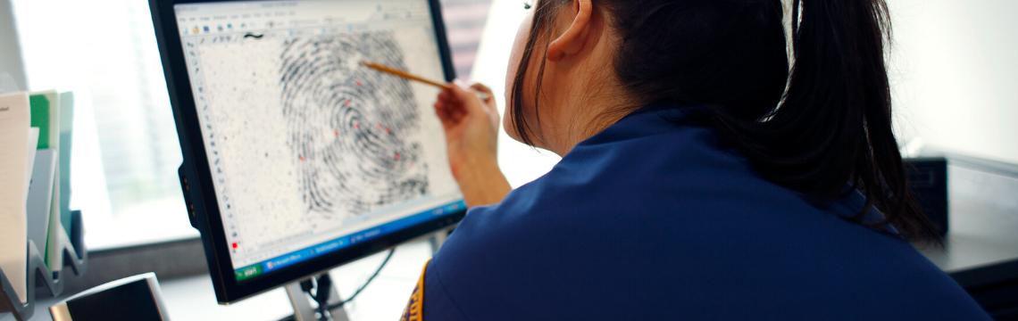 Criminologist analysing fingerprints on a computer