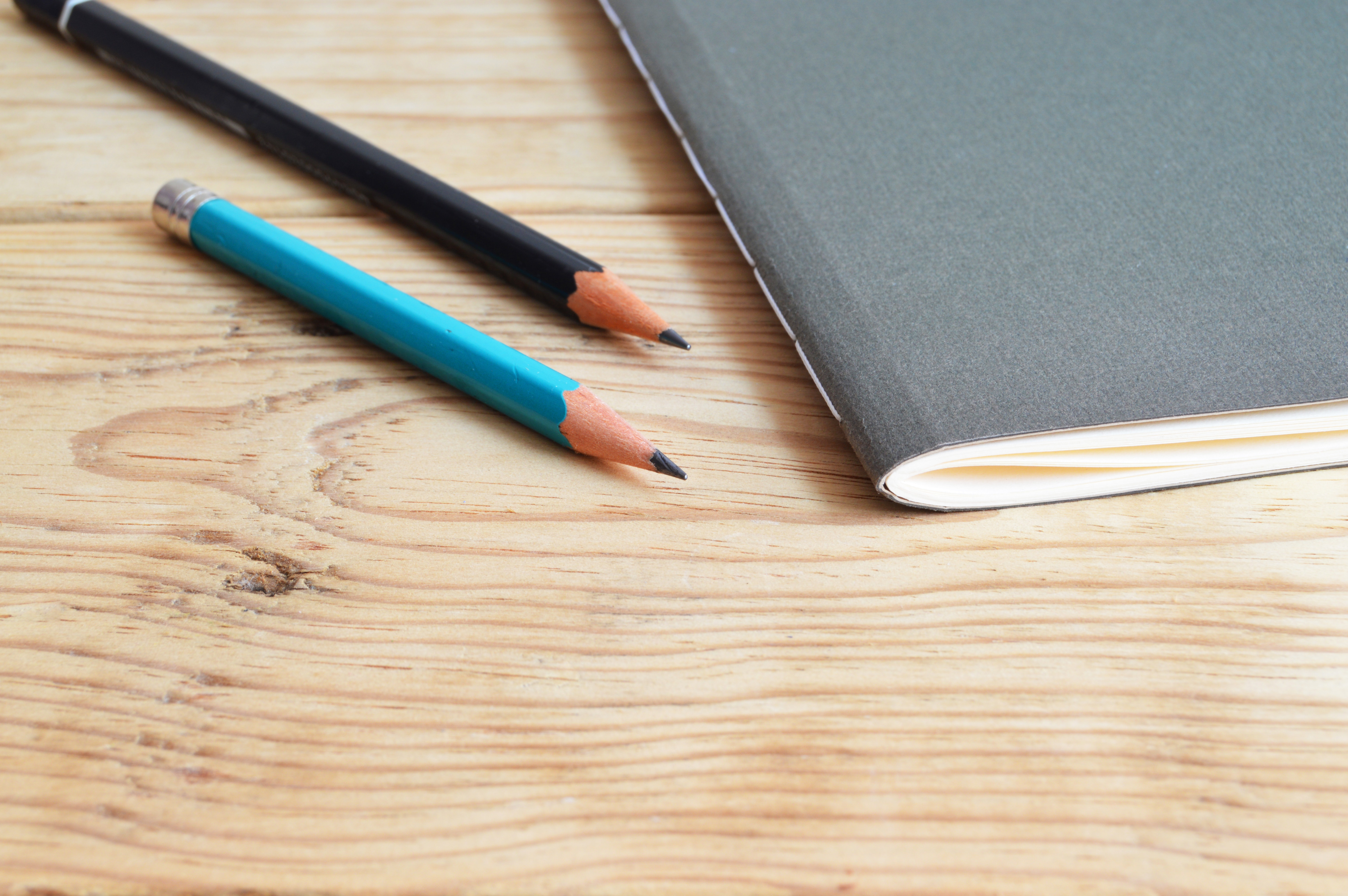 Blue and black pencil pictured next to a grey notebook