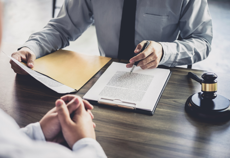 Businessman holding a pen whilst he reviews a document