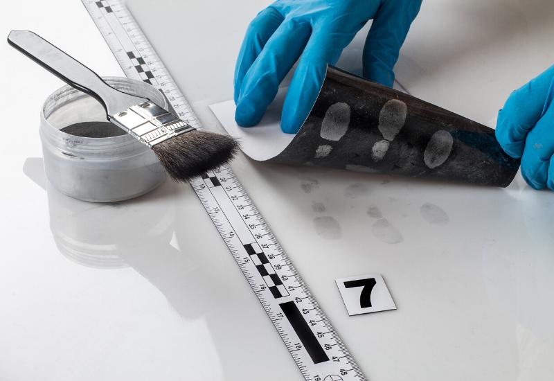 Criminologist taking finger prints at a scene of a crime