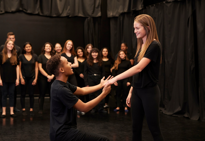 Male and female drama students pictured in black clothing pictured whilst performing
