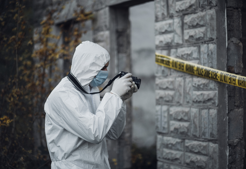 Forensic officer taking photos at a crime scene