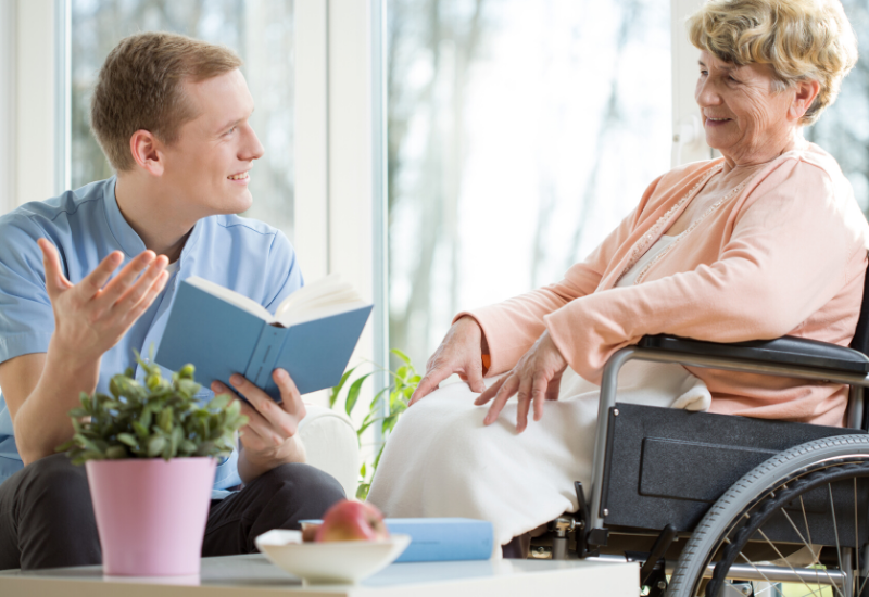 Male health and social care assistant reading a book to an elderly woman