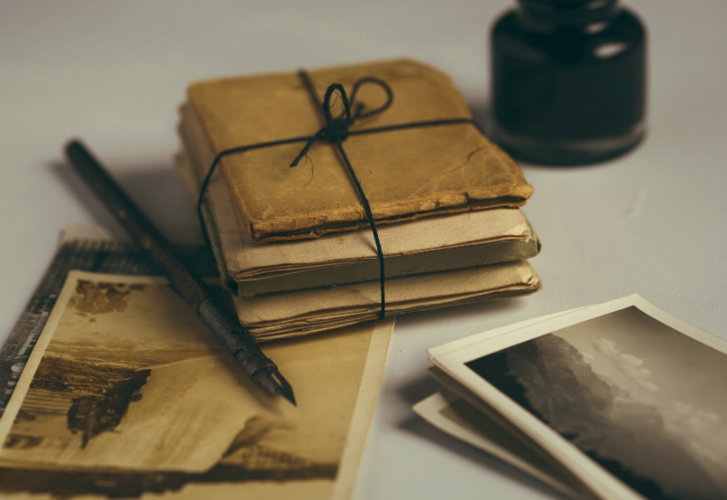 Old historic books tied up with a piece of string and an array of black and white photographs