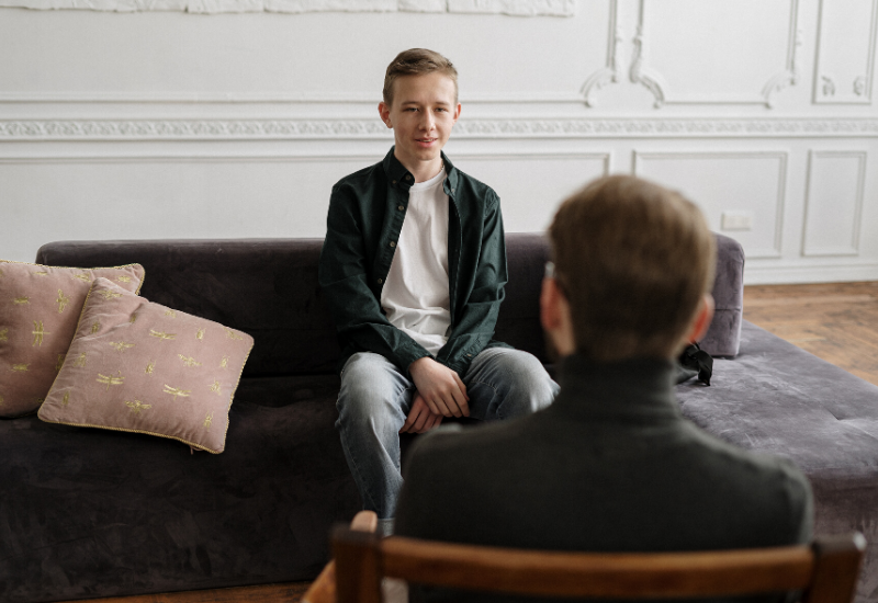 Young male speaking to Psychologist in his office