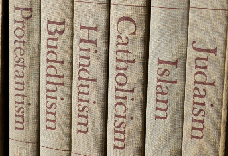Picture showing the spine of books with different religions titled